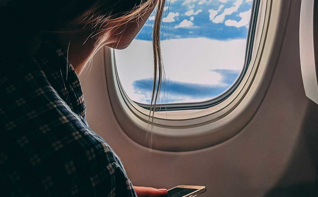 Frau guckt aus dem Flugzeugfenster