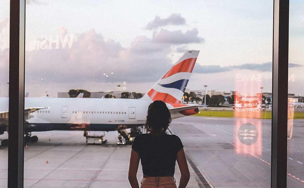 Frau schaut aus Fenster am Flughafen